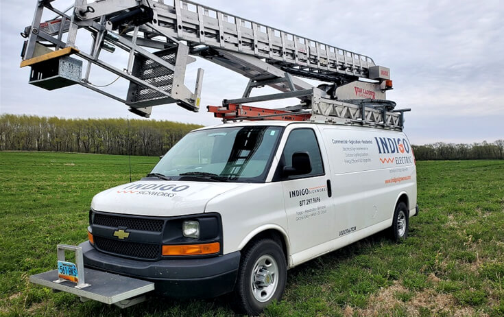 Indigo Signs Electric Ladder Van Parked in Field