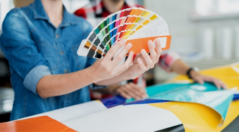 Crop view of young man and woman exploring palette of colors and choosing shades